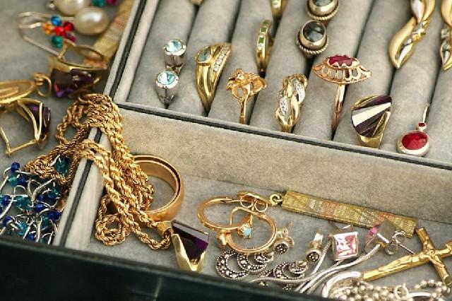 Imagem de um porta joias, com anéis, brincos, correntes, pingentes