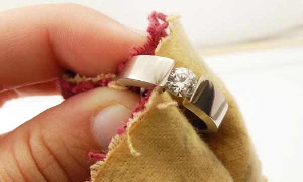 Uma mão segurando a flanela e limpando um anel